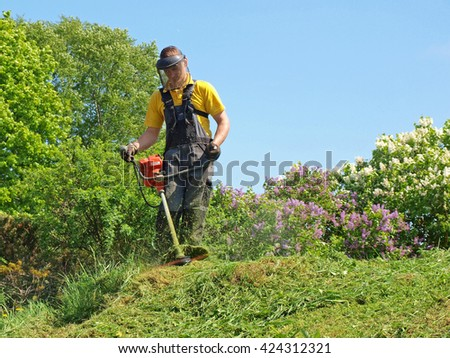 NICA, LATVIA - MAY 21, 2016: Adult man is mowing grass with string lawn mower.