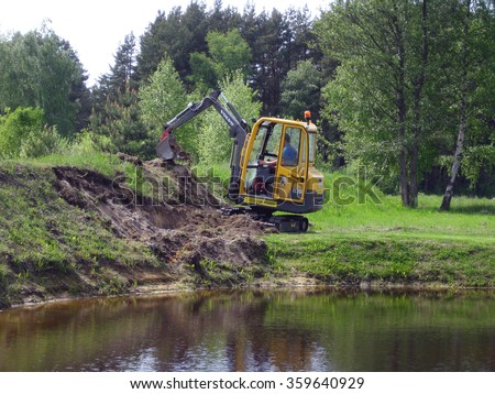 NICA, LATVIA - MAY 24, 2009: Small mini excavator is digging the ground near pond. - stock photo