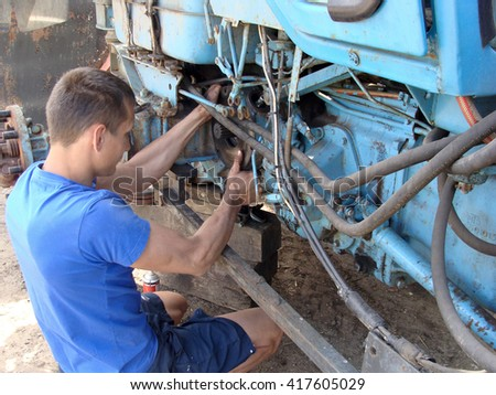 NICA, LATVIA - MAY 9, 2016: Young man mechanic is sitting on ground and mounting tractor rear wheel brakes disk. - stock photo