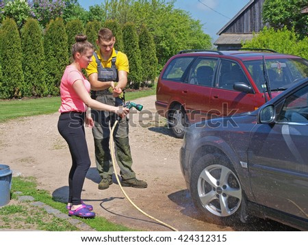 NICA, LATVIA - MAY 21, 2016: Young woman and man are washing the grey car outdoor in yard. - stock photo