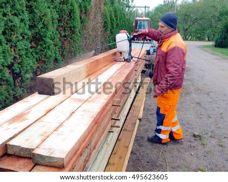 NICA, LATVIA - OCTOBER 9, 2016: Adult man worker is impregnating stacked timber with preservative liquid by garden sprayer.