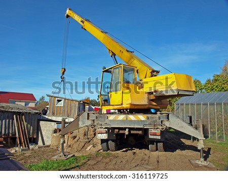 NICA, LATVIA - OCTOBER 12, 2013: Mobile crane mounted on russian truck ZIL is working to cover the new cellar with concrete panels. - stock photo