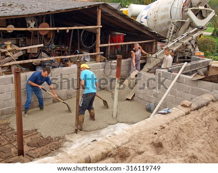 NICA, LATVIA - SEPTEMBER 14, 2013: Workers are filling foundation ditch with liquid concrete from big mobile truck cement mixer to make the cellar floor. - stock photo