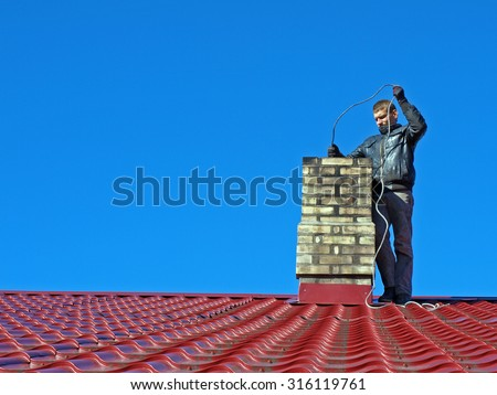 NICA, LATVIA - SEPTEMBER 25, 2013: Young man in black dresses is standing on red roof and cleaning chimney with metal brush on long cable. - stock photo