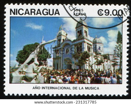 "NICARAGUA - CIRCA 1985: a stamp printed in Nicaragua shows crowd of people near the entrance to the Church of Nicaragua.  Series of stamps ""Year of international music"", circa 1985 - stock photo"