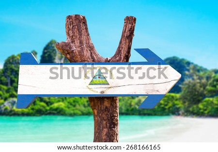 Nicaragua Flag wooden sign with beach background - stock photo