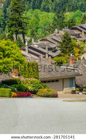 Nice and comfortable great neighborhood. Homes, roofs of the houses on the empty street in the suburbs of Vancouver, Canada. Vertical. - stock photo