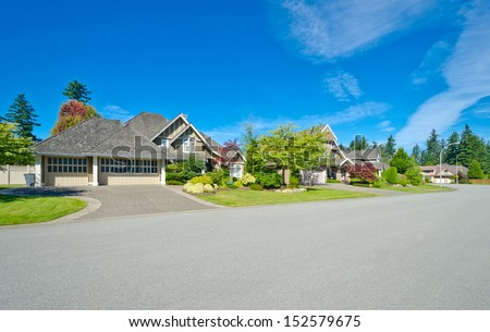 Nice and comfortable neighborhood. Empty street with a row, line of the houses, homes in the suburbs of the North America. Canada. - stock photo