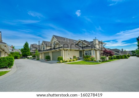 Nice and comfortable neighborhood. Houses with double doors garages on the corner of empty street in the suburbs of Vancouver, Canada. - stock photo