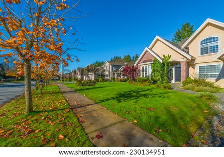 Nice and comfortable neighborhood in a fall, autumn time. Some homes in the suburbs of the North America. Canada. - stock photo
