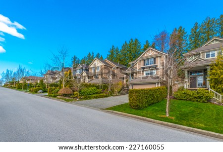 Nice and comfortable neighborhood. Perspective, outlook at some homes on the empty street in the suburbs of Vancouver. Canada. - stock photo