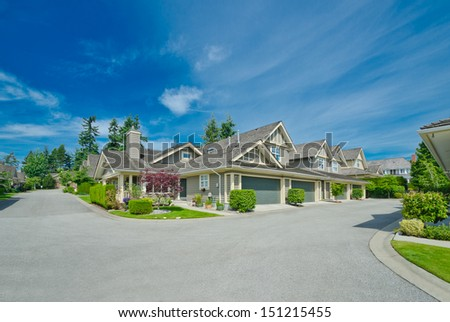 Nice and comfortable neighborhood. Some homes and garages on the empty street in the suburbs of the North America. Canada. - stock photo