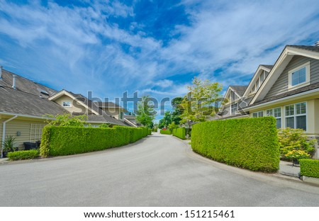 Nice and comfortable neighborhood. Some homes and garages on the empty street with nicely trimmed green fences in the suburbs of the North America. Canada. Landscape design. - stock photo