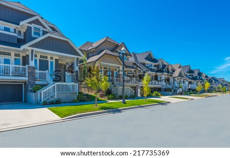 Nice and comfortable neighborhood. Some homes on the empty street in the suburbs of the North America. Canada. - stock photo