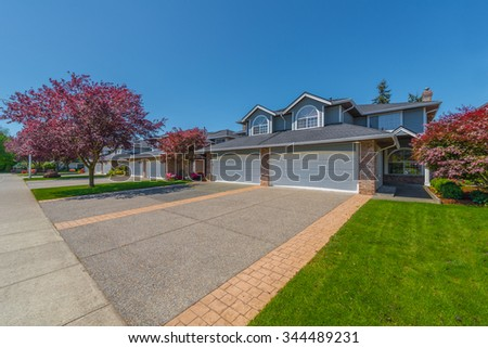 Nice and comfortable neighborhood. Some homes with driveways to garage on the empty street in the suburb of North America. Canada. - stock photo