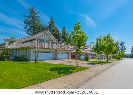 Nice and comfortable neighborhood. Some homes with garages on the empty street in the suburbs of Vancouver, Canada. - stock photo