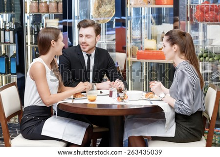 Nice and easy conversation with the coworkers by lunch. Three managers in business attire sitting around the lunch table and chatting  - stock photo