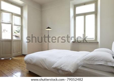 nice apartment refitted, bedroom with a double bed and lamps - stock photo