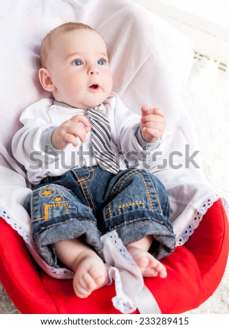 Nice baby boy sitting in car seat - stock photo