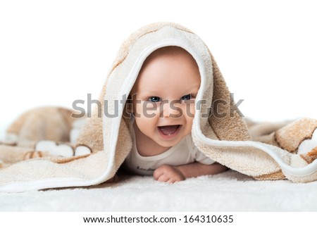 Nice  baby is laughing under the  beige carpet - stock photo