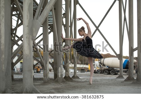 Nice ballerina posing leaning on a concrete support structure. She stands on the toe of the left foot in black tutu. Behind her is a parking for technical cars. Outdoor. Horizontal.