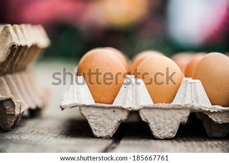 Nice big rural fresh eggs in cardboard egg box holder with colorful blurred background - stock photo