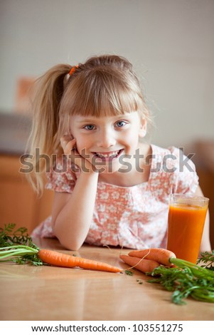 Nice blond baby girl with glass of carrot juice - stock photo