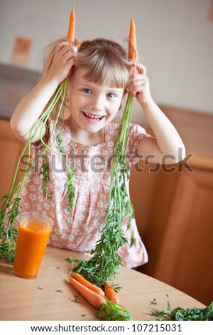Nice blond baby girl with glass of carrot juice. She represents a hare. - stock photo