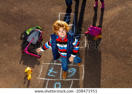 Nice blond boy jumping over hopscotch game after school with bags and scooter laying near - stock photo