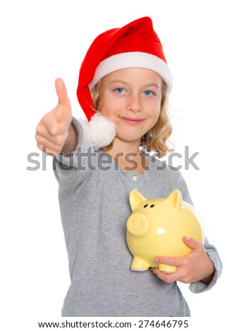 nice blond girl with Santa- cap, piggy bank and thumb up - stock photo