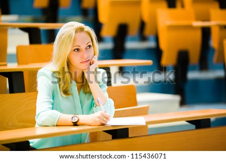 Nice blonde blue-eyed bored student girl in auditorium listening and propping up her head with a hand - stock photo