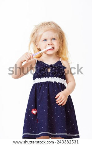 Nice blonde haired baby girl cleans teeth on white background - stock photo