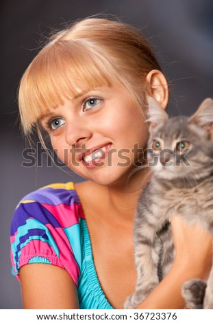 Nice blonde holds in hands of grey cat and smiles. - stock photo