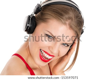 Nice blonde listening music on headphones, isolated over white background. Happy disco showgirl enjoying a song.