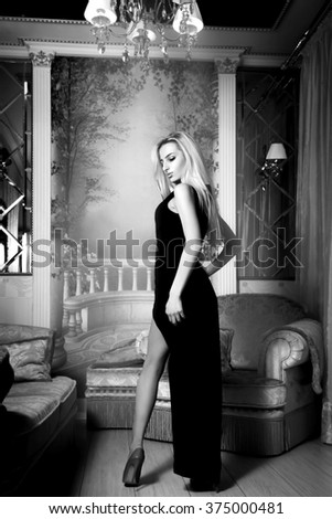 Nice blonde sexy woman in long black dress and high heels looking away. Elegant woman. Luxury life. High society.
