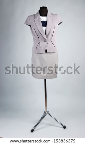 Nice blouse, gray jacket and gray skirt on mannequin,  on gray background