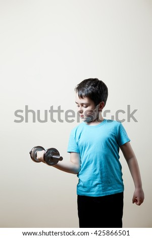 nice boy lifting dumbbell on biceps