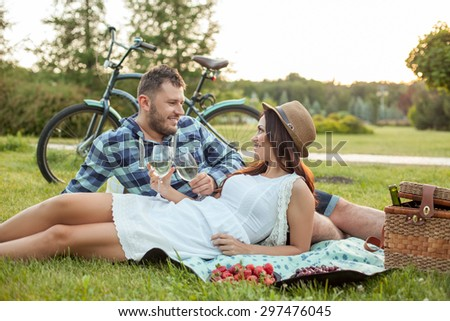 Nice boyfriend and beautiful girlfriend are on the picnic. They are drinking wine from glasses and looking at each other with love. They are smiling with happiness - stock photo