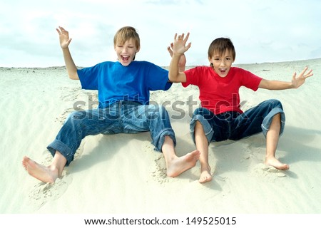 nice boys sitting on the sand in the summer - stock photo