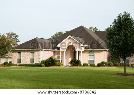 nice brick home on sweeping lawn - stock photo