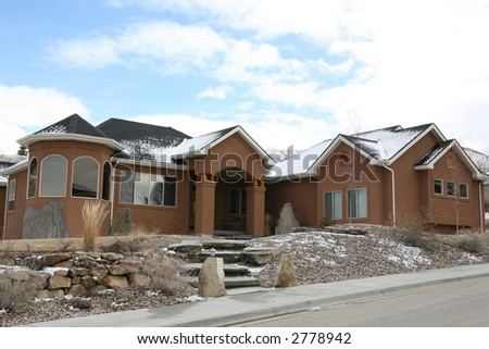 Nice brown house on a hill with snow - stock photo