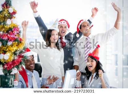 Nice business team punching the air to celebrate christmas against snow - stock photo