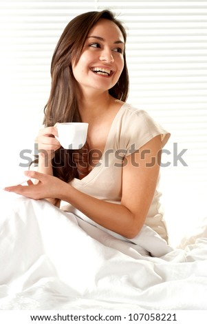 Nice Caucasian female sitting on a bed with a cup on a light background - stock photo