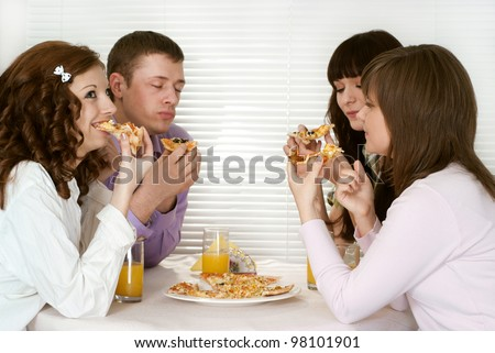 Nice Caucasian group of four people with pizza and juice sitting in a cafe - stock photo