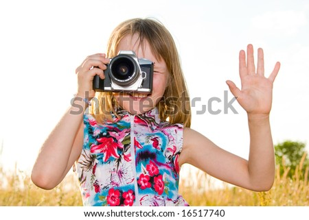 Nice caucasian little girl taking picture with SLR camera