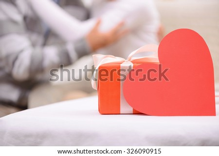 Nice celebration. Selective focus of present and heart standing on the table with adult pleasant couple sitting and embracing on the background - stock photo