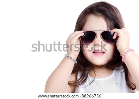 Nice child girl wearing a grey shirt isolated on white, wearing sunglasses, with her hands on the sunglasses. - stock photo