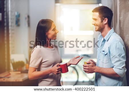 Nice coffee break. Two cheerful young people holding coffee cups and talking while standing in office  - stock photo