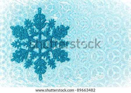 Nice cold toned image of a snow flake on a patterned background - stock photo