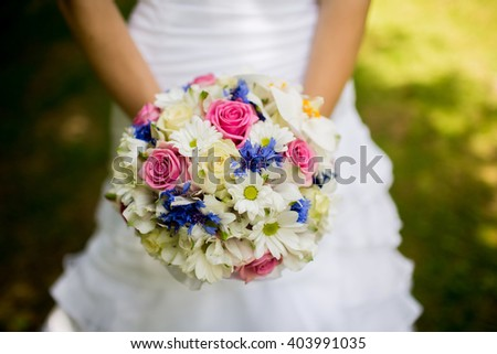 Nice colorful wedding bouquet in hands of the bride